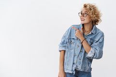 Indoor shot of pleasant stylish dreamy girl with short blond hair in glasses and denim jacket pointing looking at upper. Left corner with fascinated happy stock image