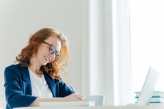 Indoor shot of pleased cheerful famale with ginger hair, signs contract, sits at cabinet in front of laptop computer. Smiling royalty free stock images
