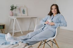 Indoor shot of relaxed female dressed in pyjamas, sits on chair, keeps legs on bed, drinks hot coffee, poses against domestic inte royalty free stock image
