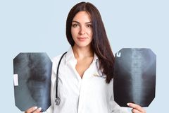 Indoor shot of serious brunette female doctor with two X rays films, examines human`s spine, wears white robe with stethoscope, st stock images