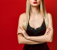Indoor shot of serious strict young female dressed velvet dress keeping arms folded royalty free stock photography
