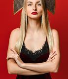 Indoor shot of serious strict young female dressed velvet dress keeping arms folded royalty free stock image