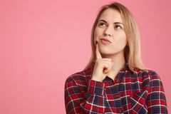 Indoor shot of thoughtful young woman holds fore finger near chin, focused up, daydreams about something, wears checkered shirt, royalty free stock photo