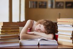 Indoor shot of tired student sleeping on book in reding room, being exhausted of studying, falling asleep while reading tutorial. Material for classes stock image
