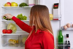 Indoor shot of young female with long straight dark hair, puts vegetables on shelf of refrigerator, eats only healthy food. Woman stock photography
