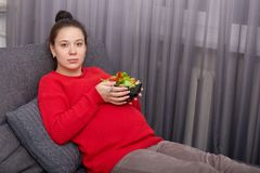 Indoor shot of young pregnant woman wears red sweater and maroon leggins, holding bowl of salad in both hands, model looks at stock image