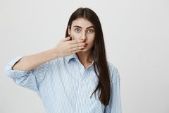 Indoor shot of young stylish woman covering her mouth with hand, looking anxious with lifted eyebrows, standing over. Gray background. Trendy woman with stylish Royalty Free Stock Images