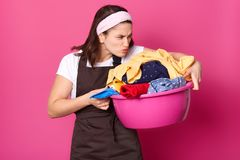 Indoor shot of young tired housewife, doing house chores, smelling dirty clothes, going to wash them, having disgusting facial. Expression, hates washing stock image