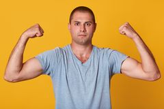 Indoor studio shot of handsome athletic young man showing muscles, raising his arms, looking directly at camera, being confident stock photo