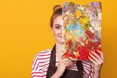 Indoor studio shot of satisfied talented girl holding palette to mix colors, covering half of her face with it, looking directly. At camera, ready to paint royalty free stock photos