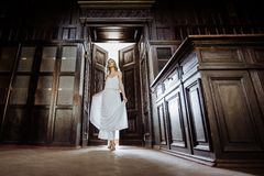 Indoor summer portrait of young pretty cute girl. Beautiful woman posing beside fairytale door inside wood cabinet, scars old cast Royalty Free Stock Image