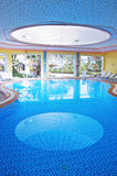 Indoor swimming pool. View of an indoor luxurious resort swimming pool Royalty Free Stock Photos
