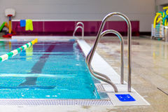 Indoor swimming pool. Empty indoor swimming pool detail view with stairs guardrails Royalty Free Stock Images