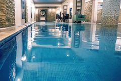 Indoor swimming pool on resort. Indoor swimming poo on resort. Spa and Wellness centre with swimming pool, bath, sauna, and restaurant inside. Swimming pool with Royalty Free Stock Photography