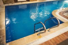 Indoor swimming pool with stair in a building. An indoor pool. blue clear transparent water Stock Photos