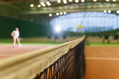 Indoor tennis court playing athlete girl Royalty Free Stock Photos