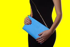 Indoor trendy girl near yellow background .Black dress and blue clutch Royalty Free Stock Photography