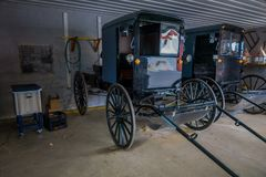Indoor view of Amish black carriage or buggy parked inside of a garage of a house in Lancaster County. Pennsylvania Royalty Free Stock Photo