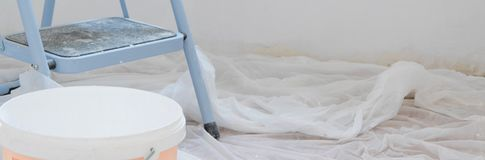 Indoor view of construction site, ladder in foreground and fresh painting walls with white color royalty free stock images