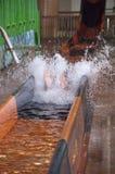 Indoor Waterpark or Water Park Slide Splash Fun. Waterpark slide splash. A young person has fun in the water at an indoor water park Stock Image