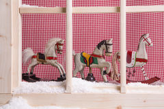 Indoor window sill Christmas decoration: rocking horses and snow Royalty Free Stock Photos