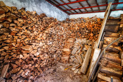 Indoor woodshed with nicely arranged chopped firewood Stock Images