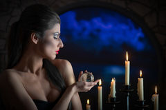 Sorceress with the glass sphere. Indoors close-up portrait of a sorceress with the glass sphere and the candles Stock Image