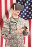 Indoors close up shot of military man wearing VR goggles and controller in hands. Filtered image: cross processed vintage effect. Indoors close up shot of Stock Photography