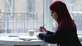 Indoors footage of beautiful muslim girl with hijab on her head typing something and then writing something down in her. Notebook stock footage