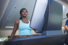 Indoors gym portrait of young attractive and sweaty black afro American sporty woman training treadmill running and walking workou stock photo
