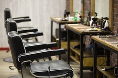 Indoors image of barbershop. Row of black leather chairs in modern barber shop interior. Horizontal indoors shot Stock Photography