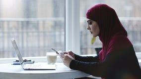 Indoors materiał filmowy atrakcyjna muzułmańska dziewczyna używa różnych gadżety tak jak smartphone i laptop zdjęcie wideo