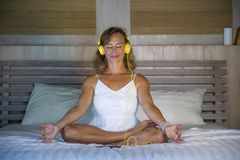 Indoors portrait of beautiful and fit healthy woman 30s practicing yoga listening to music with headphones in bed posing calm and. Relaxed concentrated in stock photo