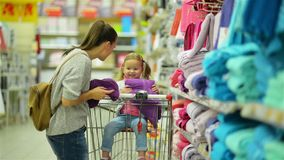 Indoors Portrait of Happy Female Child and Her Attractive Mother in Hypermarket Choosing Violet Towel Together Standing stock footage