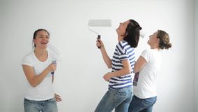 Indoors Portrait of Three Funny Female Friends Doing Home Repairs, Dancing and Singing in the Paint Roller. stock footage