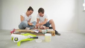 Indoors Portrait of Young Happy Family Choosing Colors for Their New Flat. Woman and Man are Sitting on the Floor with stock footage