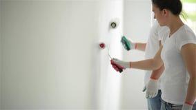 Indoors portret Aktywna Szczęśliwa para Robi mieszkanie naprawie Wpólnie Młoda Dziewczyna i mężczyzna w koszula i cajg farbie zbiory wideo