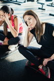 Indoors shot of beautiful girl resting after fitness training. tired young girl sitting break after exercising in gym Royalty Free Stock Photos