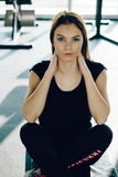 Indoors shot of beautiful girl resting after fitness training. tired young girl sitting break after exercising in gym Royalty Free Stock Photography