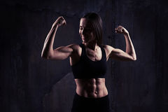 Indoors shot of young confident muscular woman showing the relie Royalty Free Stock Photo