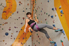 Indoors training. Cheerful Vietnamese girl practicing climbing on rock wall indoors Stock Image