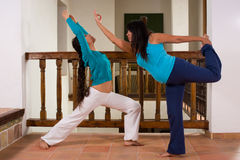 Indoors yoga. Mother and daughter enjoying a yoga session indoors Stock Photos