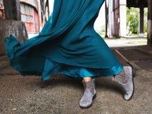 Indossando un turchese, nel vestito d'ondeggiamento dal vento, stivali grigi della caviglia, fotografati alla vita fotografia stock libera da diritti