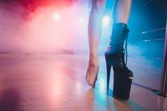 Indossi gli alti stivali uno sulla piattaforma e sul tallone ballerino di striptease che si muove in scena in night-club della st fotografie stock libere da diritti
