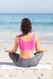 Indossi il punto di vista della donna di misura che fa l'yoga accanto al mare fotografie stock libere da diritti