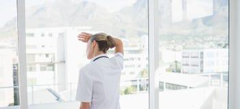 Indossi il punto di vista di medico femminile sicuro che guarda attraverso le finestre fotografia stock