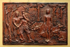 Indra prevents an ignorant cowherd from assaulting Bhagavan Mahavira. Street bass relief on the wall of Jain Temple also called Parshwanath Temple in Kolkata royalty free stock photography