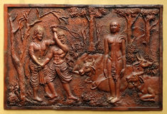 Indra prevents an ignorant cowherd from assaulting Bhagavan Mahavira. Street bass relief on the wall of Jain Temple also called Parshwanath Temple in Kolkata stock photography