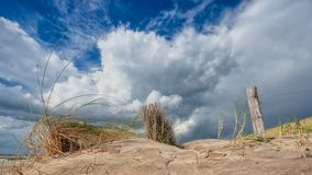 Indrukwekkende witte en grijze onweerswolken over duinlandschap  stock afbeelding