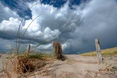 Indrukwekkende witte en grijze onweerswolken over duinlandschap  stock foto